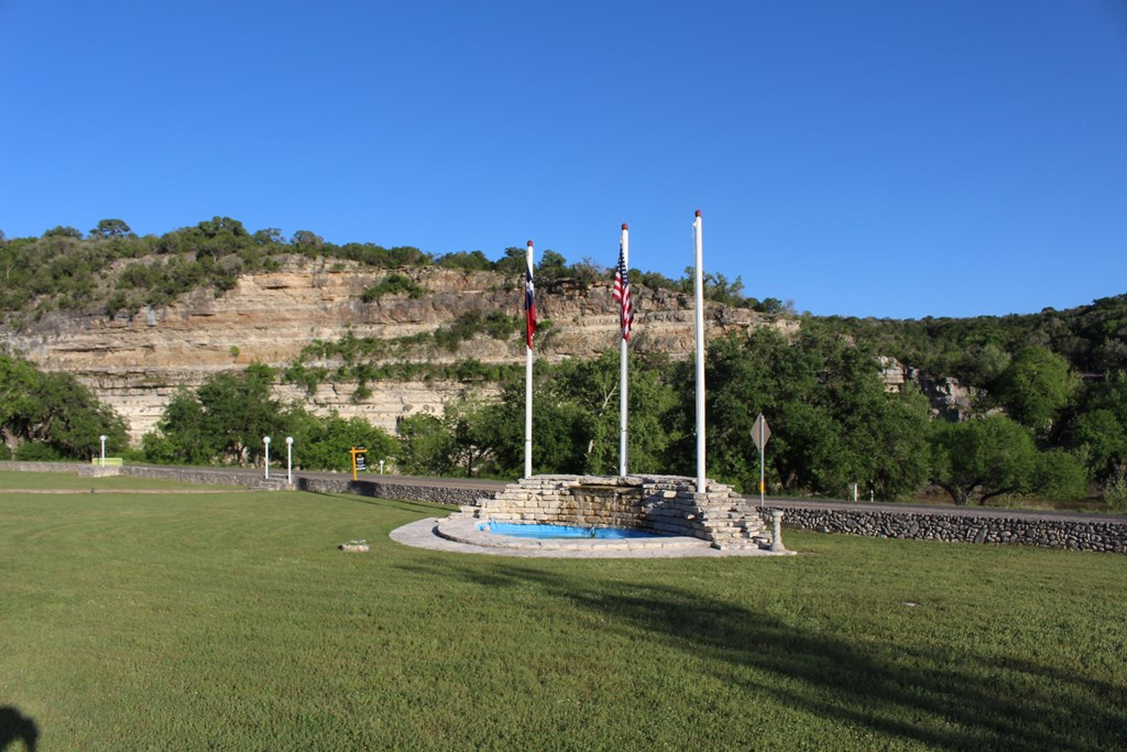 Three flag poles with a rock waterfall below
